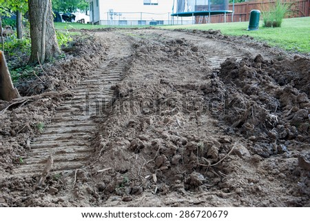 A backyard is scarred by dirt tracks from a front-loader or bulldozer