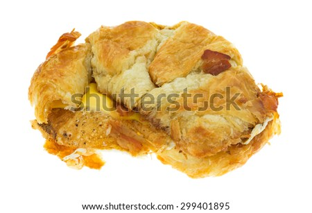 A bacon egg and cheese croissant breakfast sandwich with a bit of bacon on the crust isolated on a white background. - stock photo