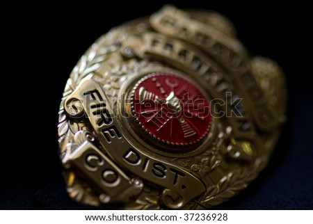 A badge from a fire fighter on a dark background - stock photo