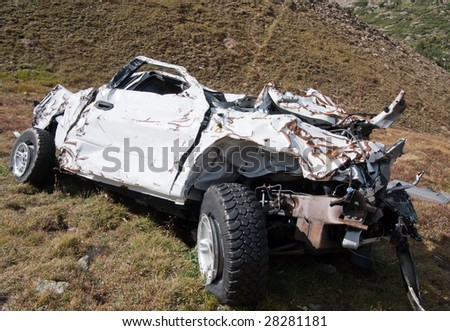 A badly wrecked vehicle involved in a rollover accident.
