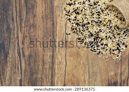 A bag of different types of rice dropped over a floor - stock photo