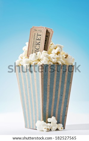 a bag of popcorn and cinema tickets with blue background - stock photo