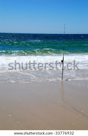 A baited fishing pole set to catch a fish in the surf on the beach. - stock photo