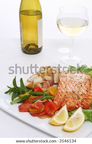 A baked salmon dinner with vegetables and potatoes and a glass of wine