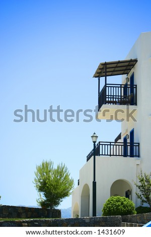 A balcony of a greek whitewashed stone villa overlooking the sea - stock photo