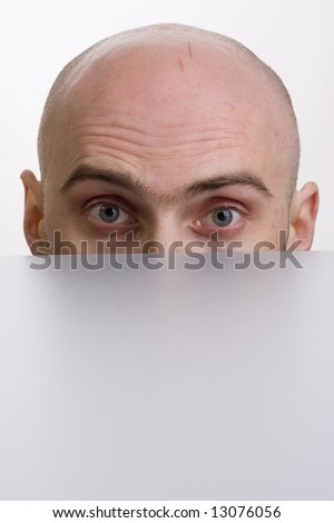 A bald man is peering over a wall with his brow furrowed. - stock photo