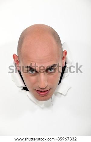A bald man popping through a wall. - stock photo
