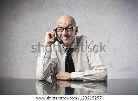 A bald office worker smiles while is calling someone with a mobile phone