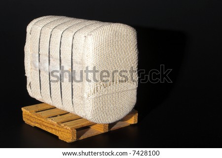 A bale of raw cotton on a pallet. - stock photo