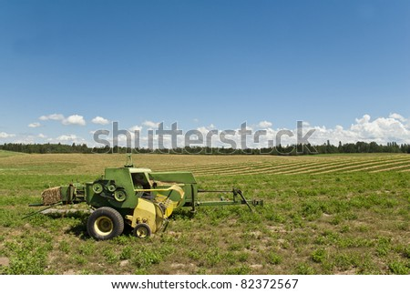 A baler waits in a high country field of mown hay.