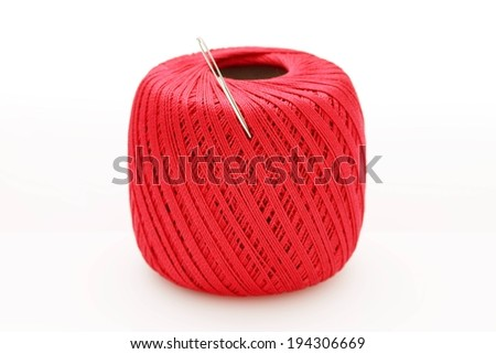 A ball of red string with a needle stuck into it. - stock photo