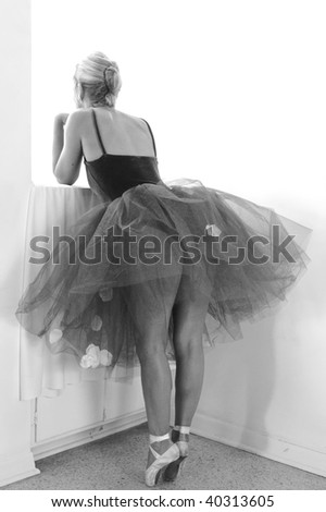 A ballerina is turned away looking out window while standing on toes in this black and white image. - stock photo