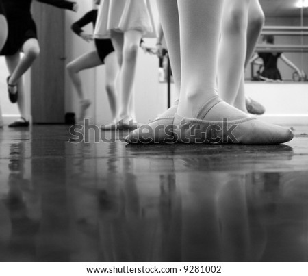 A ballerina practicing moves in the studio with others... a bit of noise exists in the image - original ISO 1600 but i've cleaned it up a good bit tho some noise is still evident. Black and white - stock photo