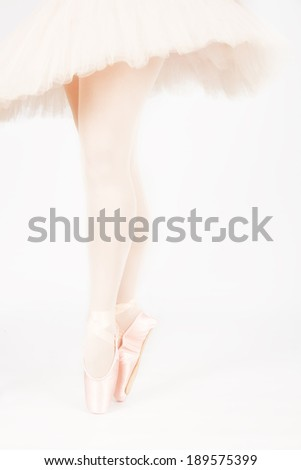 A ballet dancer standing on toes while dancing on pink background artistic conversion - stock photo