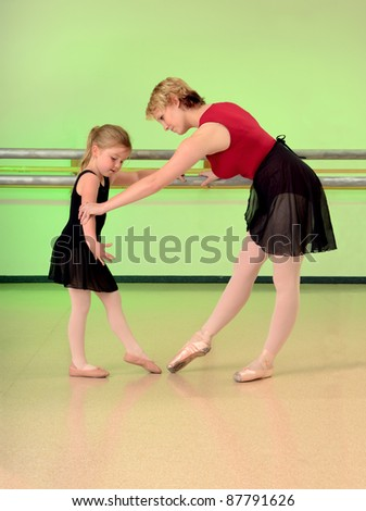 A Ballet Teacher Helps a Girl Dance Student with her lesson - stock photo