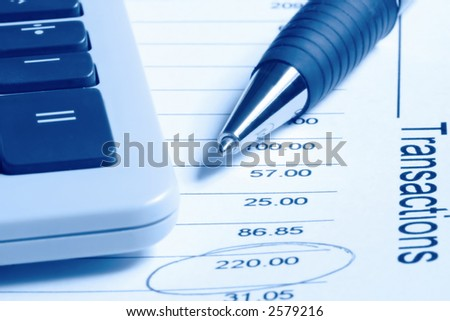 A ballpoint pen and calculator on a financial statement.  Blue duotone. - stock photo