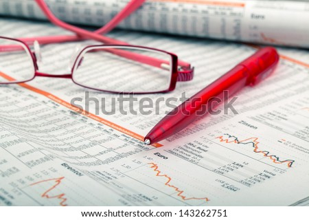 a ballpoint pen and reading glasses on a newspaper - stock photo
