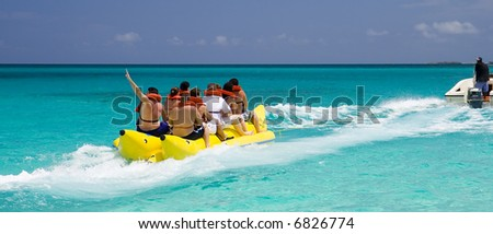 A Banana Boat Full of Tourists Speeding Away - stock photo
