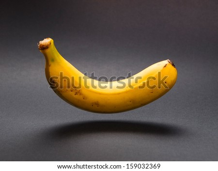 A banana floating in the air in a studio shot. - stock photo
