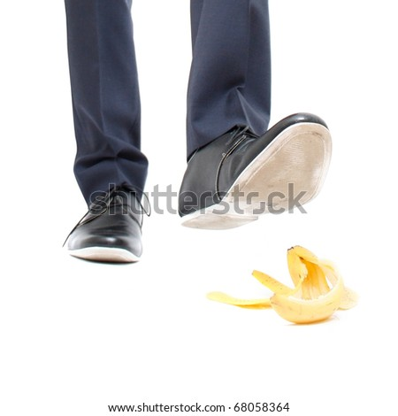 A banana peel and a man about to step in it - stock photo