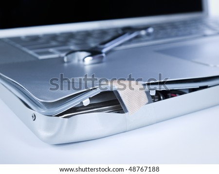 A band aid is fixing a damaged laptop. A spanner is over the computer. - stock photo