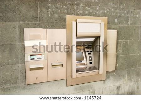 A bank machine on a stone wall. - stock photo