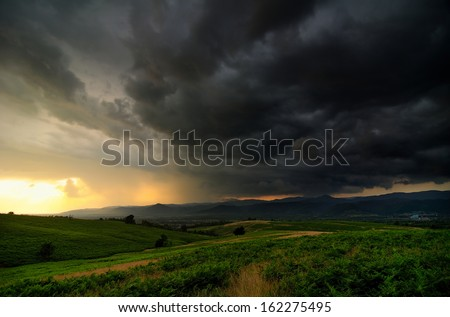 A bank of angry storm clouds on sunset's light - stock photo