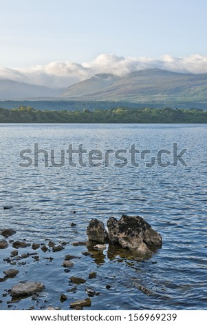 A bank of cloud lies on top of Mangerton mountain, viewed across the calm waters of Lough Leane, Lower Lake, Killarney, Ireland on a peaceful summer morning. - stock photo