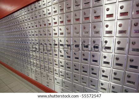 A bank of post office boxes in a post office foyer.