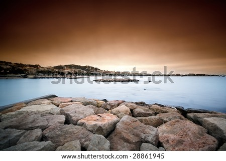 A bank of rocks over the bay of Cannes with silky water and a red sky in the sunset light - stock photo