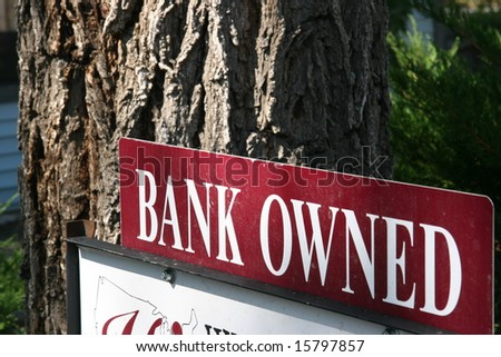 A bank owned sign in front of a house in foreclosure - stock photo
