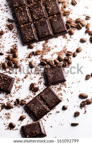 A bar of dark chocolate and some coffee beans on a white surface - stock photo