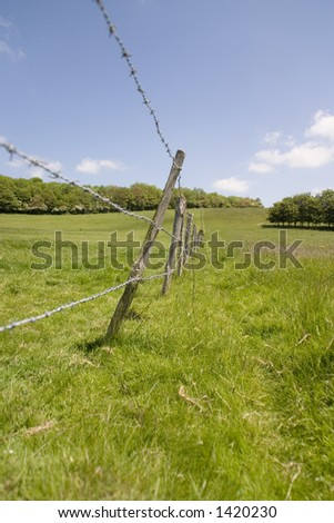 A barbed wire fence in a field extending into the distance. - stock photo