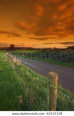A barbed-wire fence running alongside a typical country road in rural Warwickshire, England, with sunset sky in the background. - stock photo