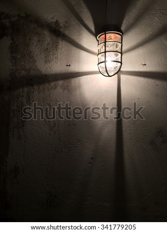 A bare bulb with cage around it mounted on concrete wall in underground tunnel. - stock photo
