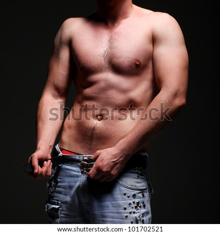 A bare-chested handsome young man in jeans showing his abs - stock photo