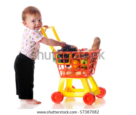 "A barefoot baby girl ""shopping"" for groceries with a toy shopping cart.  Isolated on white. - stock photo"