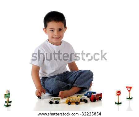 A barefoot kindergarten boy playing with an assortment of cars, trucks and traffic signs.  Isolated on white. - stock photo