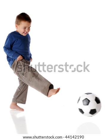A barefoot preschooler kicking a soccer ball.  Isolated on white.  (Ball has motion blur.) - stock photo