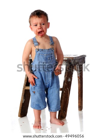 A barefoot preschooler messy from a fudgecycle crying beside an battered step stool.  Isolated on white. - stock photo