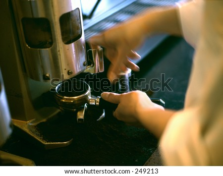 A barista grinding a shot of espresso and making a shot of espresso. - stock photo