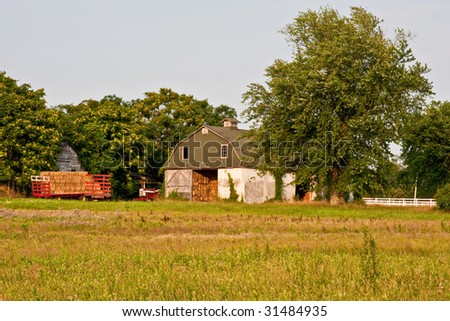 A barn in the country with a trailer full of hay. Photo was captured in late evening sunlight.