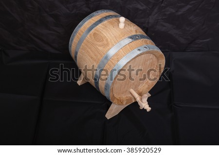 A barrel of alcohol on a black background. - stock photo