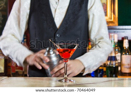 A bartender makes a cocktail over the marble bar counter - stock photo