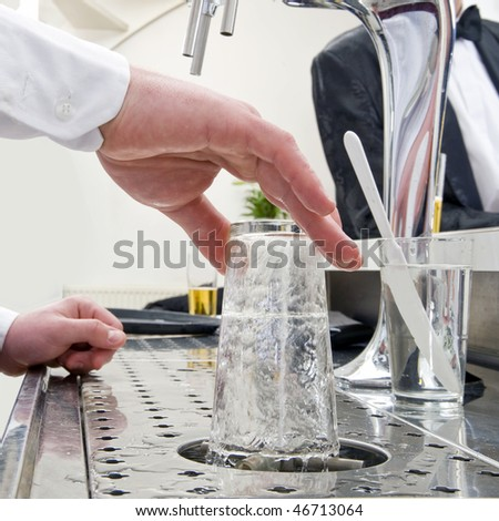 a bartender rinsing a beer glass at his bar with customers at the background - stock photo
