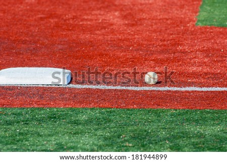 A base and a ball on an infield of a baseball field - stock photo
