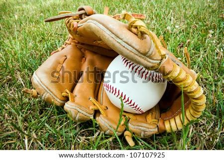 a baseball and an old baseball glove lying on the a baseball field. - stock photo