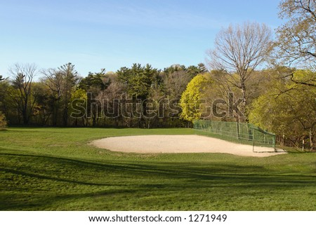 A baseball diamond field surrounded by trees. - stock photo