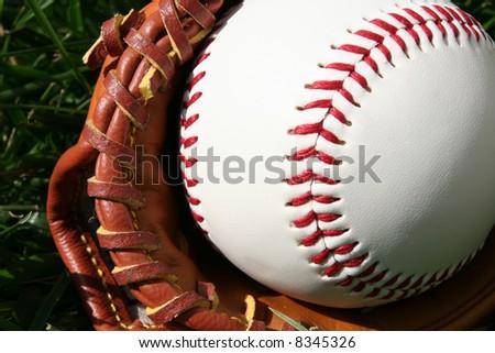 A baseball glove with a baseball - stock photo