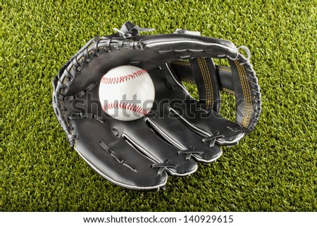 A baseball inside a black glove over green field - stock photo